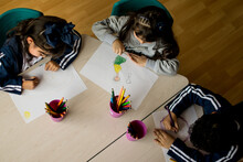 Tres Niños Dibujando En Una Mesa En El Colegio Visto Desde Arriba