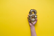 Girl's Kid Hand Holds A Golden Helium Balloon Number 8 On A Yellow Background. International Women's Day And March 8