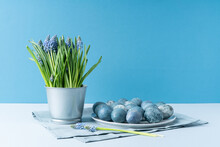 Easter Eggs And Muscari In Decorative Bucket On Light Blue Background.