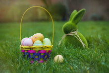 Easter Basket With Colored Eggs And Easter Bunny Rabbit Statuette On The Green Grass With Dew. Easter Egg Hunt In The Garden. Safe Festive Tradition During Pandemic. Selective Focus, Copy Space.