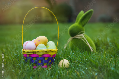 Slika na platnu Easter basket with colored eggs and Easter bunny rabbit statuette on the green grass with dew