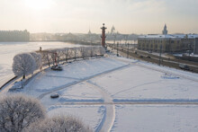 Aerial View Of Red Rostral Column On Vasilyevski Spit In Winter With Frosty Trees In The Foreground