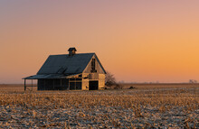 An Old, Wooden Corn Crib Stands In A Field Of Harvested Corn, While The Sunrise Paints Everything With A Golden Orange Light.