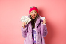 Shopping And Fashion Concept. Excited Asian Senior Woman Going Buy Something With Money And Plastic Credit Card, Scream Of Joy And Happiness, Pink Background
