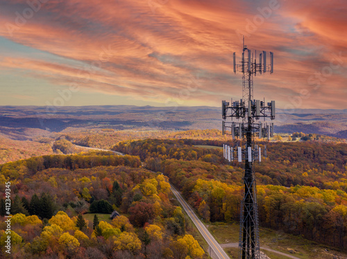 Aerial view of mobile phone cell tower over forested rural area of West Virginia to illustrate lack of broadband internet service © steheap
