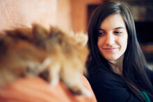 Long Haired Girl Looks At Ther Ginger Spitz Dog On A Sofa