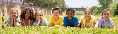 Canvas Group of school children resting on grass and smiling together in park
