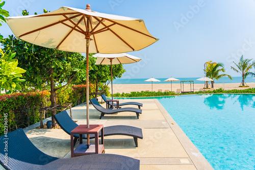 Fototapeta Umbrella and chair around outdoor swimming pool in hotel resort obraz