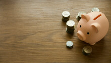 Selective Focus Of A Piggy Bank And Stack Of Coins On Wooden Background With Copy Space.