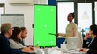 Leinwandbild Motiv Diverse woman standing in start up office discussing strategy with green screen monitor in front of business partners. Manager explaining to multiethnic team project chroma key display mock up desktop