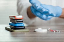 Closeup Of Man Preparing For Cleaning Mobile Phones To Protect Himself From Viruses, Sanitizing Devices Through Which The Virus Is Transmitted