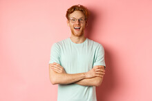 Portrait Of Cheerful European Man In Glasses Looking Amazed At Camera, See Interesting Promotion, Standing Amused Over Pink Background