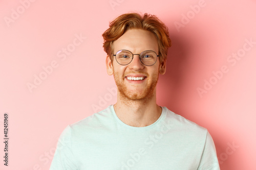 Fotografia Close up of happy redhead man face, smiling with white teeth at camera, wearing