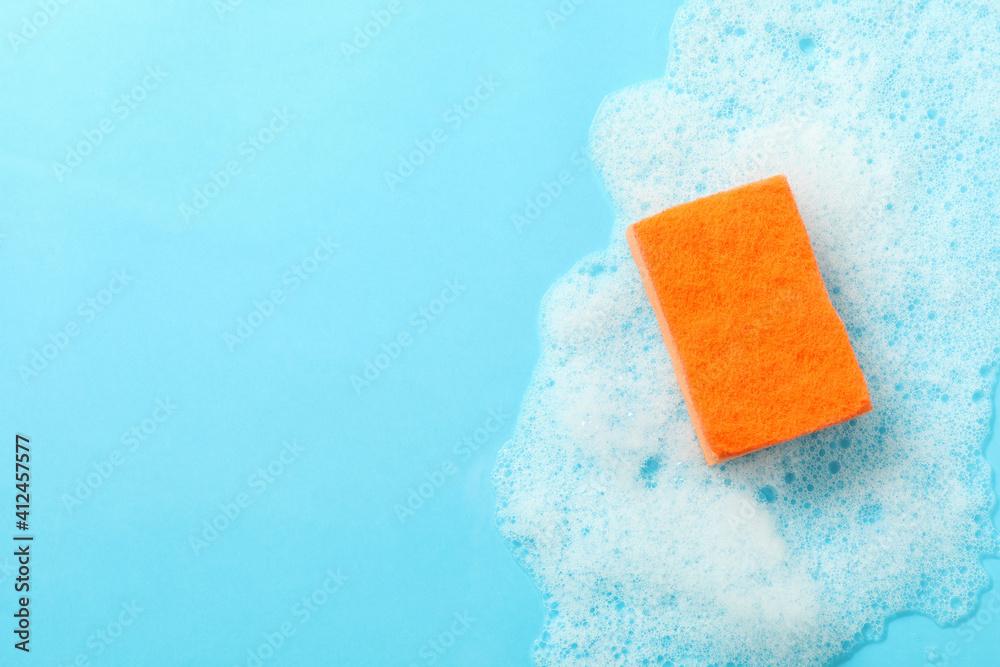 Fototapeta Orange sponge and foam on blue background