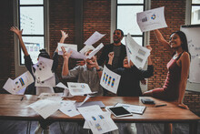 Happy Business Colleagues Throwing Documents During Meeting In Office