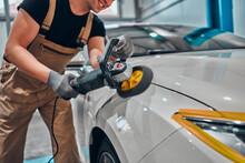Professional Auto Detailer Hand Holding Rotary Polisher While Polishing Paint Surface Of Shiny White Car.