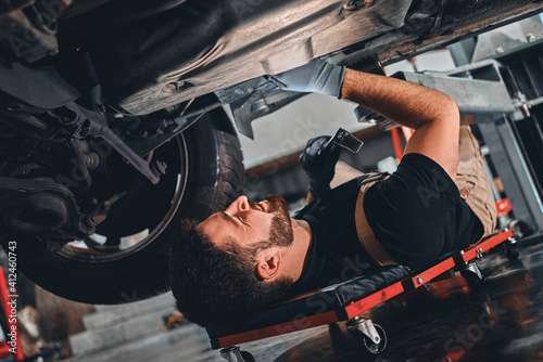 Bearded male technician in gloves lying on car creeper and using LED inspection lamp while working under automobile in garage Tapéta, Fotótapéta