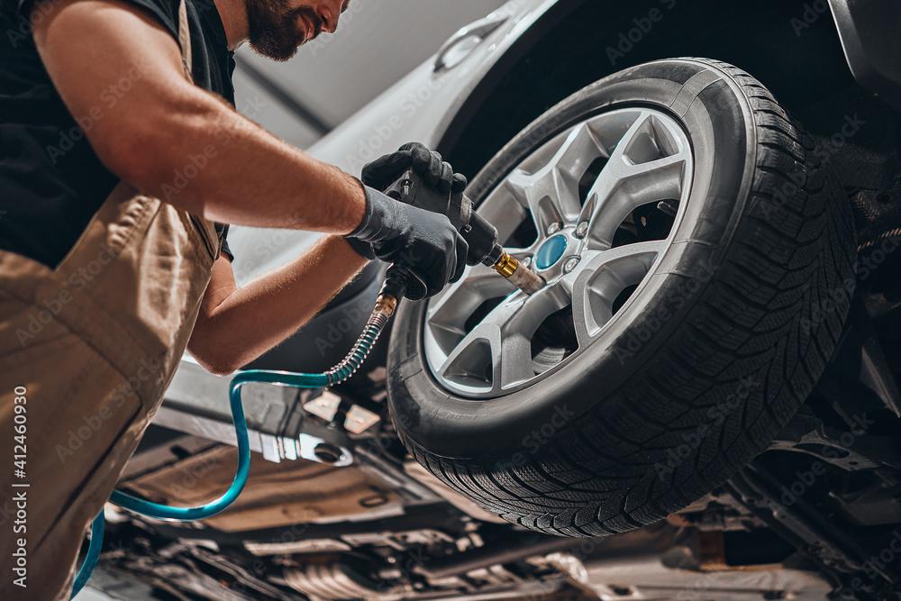Fototapeta Auto mechanic changing car wheel.