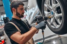 Car Mechanic Screwing Or Unscrewing Car Wheel Of Lifted Automobile By Pneumatic Wrench At Repair Service Station.