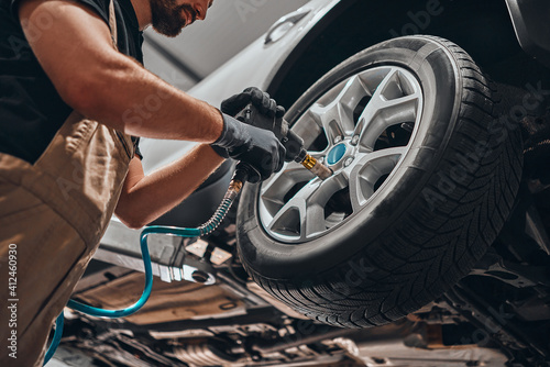 Obraz Auto mechanic changing car wheel. - fototapety do salonu