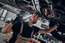 Portrait Shot Of A Handsome Mechanic Working On A Vehicle In A Car Service. Professional Repairman Is Wearing Gloves And Using A Lamp Underneath The Car.
