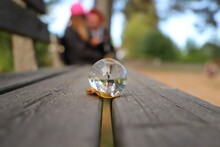 Close-up Of Crystal Ball On Park Bench