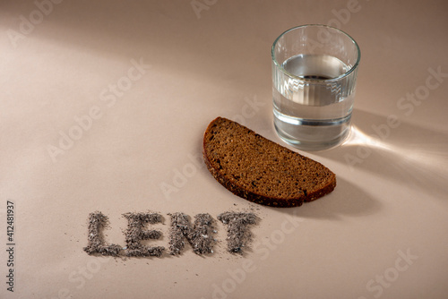 Photo Lent Season, Holy Week and Good Friday concept - water, bread and text made of ashes