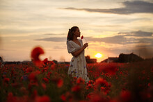 Girl In A White Dress In A Field Of Poppies On A Sunset Background