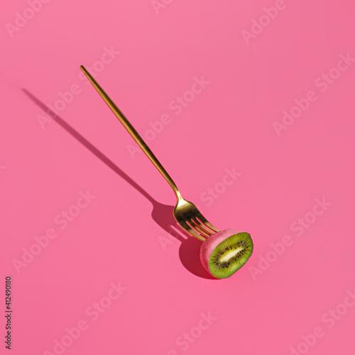 Pink kiwi sliced in half with golden fork on pink background. Creative heathy snack, food, fruit or vegetarian concept. Summer trend shadows. Surreal art scene.