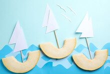 Composition With Sailboats Made Of Melon Slices On Light Blue Background, Flat Lay