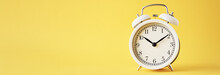White Vintage Alarm Clock On A Yellow Background, Long Banner With Copy Space