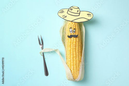 Fototapeta Mexican man made of corncob, paper hat and fork on light blue background, top view obraz