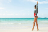 Beautiful woman wearing red swimsuit and sweatshirt walking on white sand beach
