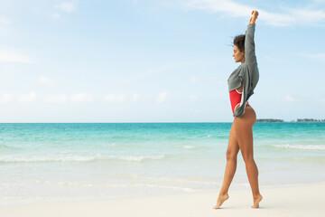 Beautiful woman wearing red swimsuit and sweatshirt walking on white sand beach