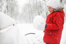 Cute Little Girl Holding Snowball Near Bench On Winter Day, Space For Text