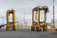 Two Straddle Carriers, Giant Vehicles Used To Move Shipping Containers, In A Cargo Terminal