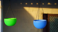 Modern Suspended Flower Pots With The Rooftop. Green And Blue Flower Basket Parallel With Each Other.