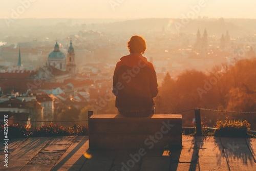 Fototapeta man looks at the city at sunset