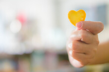 Cropped Hand Holding Yellow Heart Shape