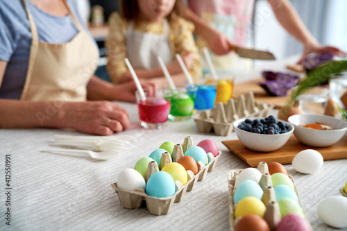 Fotografie, Obraz Close up of dyeing Easter eggs in the family circle