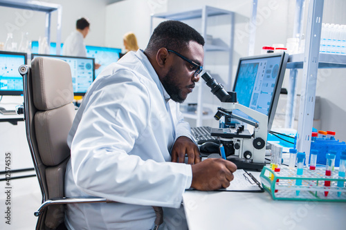 Fototapeta Professional African-American scientist is working on a vaccine in a modern scientific research laboratory. Genetic engineer workplace. Future technology and science. obraz