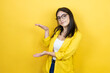 canvas print picture - Young brunette businesswoman wearing yellow blazer over yellow background gesturing with hands showing big and large size sign, measure symbol. Smiling . Measuring concept.