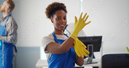 Obraz na plátně Portrait of african female janitor putting on gloves working in office
