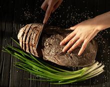 Woman Cutting Fresh Bread On Table Against Dark Background