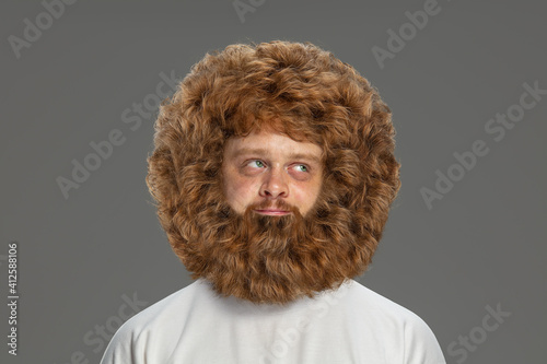 Half-length portrait of young very hairy man isolated over grey background.