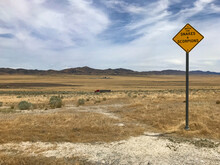 View Of Utah Desert On A Summer Day.  Snakes And Scorpions Warning Sign. 18 Wheeler Truck Passing By In The Background.