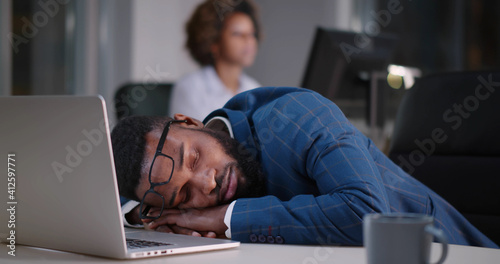 Obraz Young african businessman with eyeglasses worked late and fell asleep on desktop - fototapety do salonu