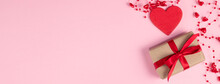 Valentine's Day Banner. Red Heart And Gift With Red Ribbon Near Beads With Hearts On Pastel Pink Colors. Valentine's Day Concept. Flat Lay.