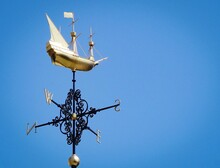 Low Angle View Of A Weathervane Against Clear Blue Sky