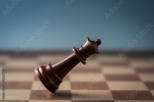 Fototapeta black chess queen falling on chess board concept of failing.